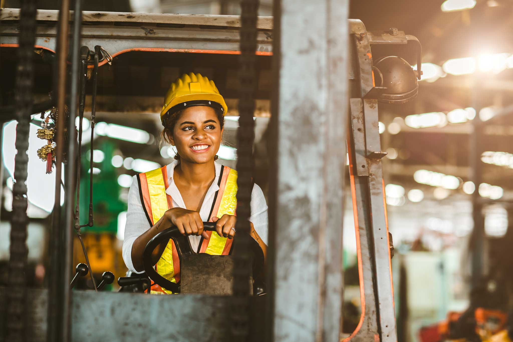American black women labor worker at forklift driver happy working in industry factory logistic shipping warehouse.